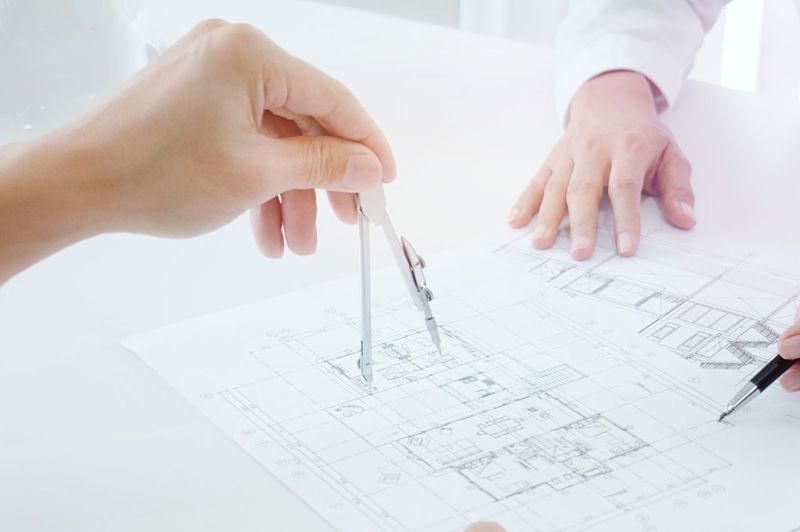 Cropped hands of engineer drawing blueprint