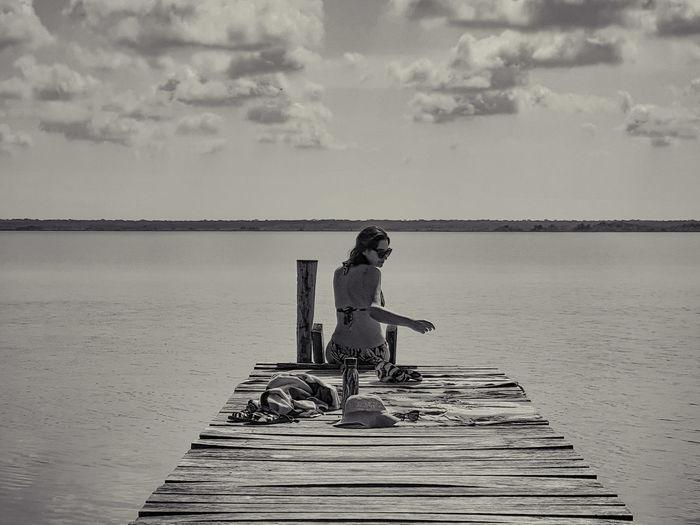 Rear view of woman wearing bikini sitting on pier over lake