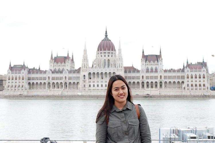 Portrait of smiling woman standing against river and hungarian parliament building in city