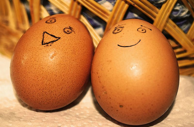 Close-Up Of Anthropomorphic Smiley Faces Drawn On Brown Eggs
