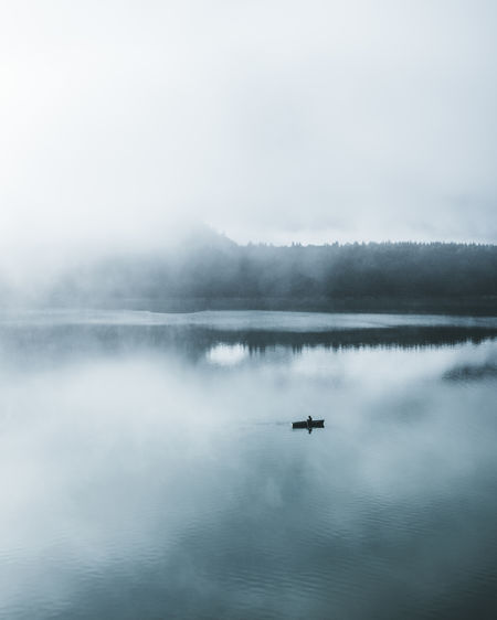 Lonely fisherman on a calm lake. My Best Photo Water Waterfront Beauty In Nature Scenics - Nature Lake Tranquility Tranquil Scene Reflection Nature Fog Sky Day No People Outdoors Boat Minimalism Fisherman Lonely Thinking Fishermen Fisherman Boat Calm Simple Simplicity