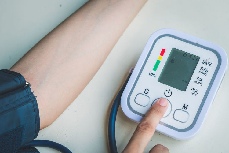 Cropped image of woman checking blood pressure on table