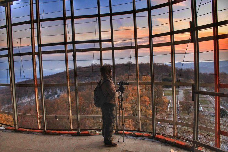 Man photographing through glass window