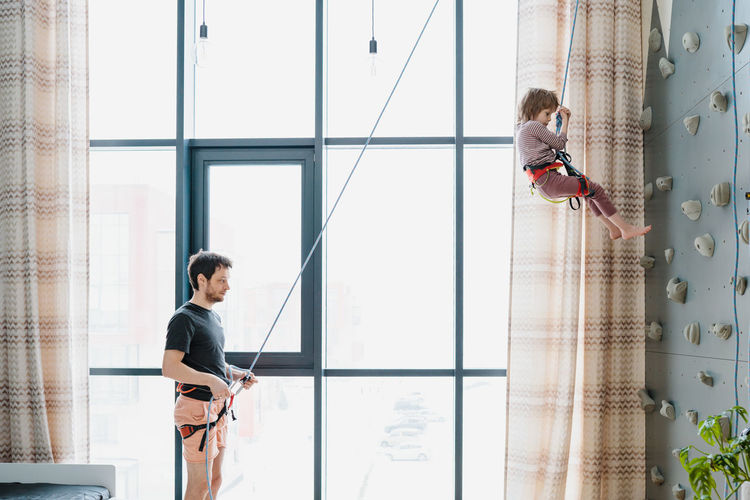 Young boy indoor rock climbing with his father instructor. hobby or home sport concept