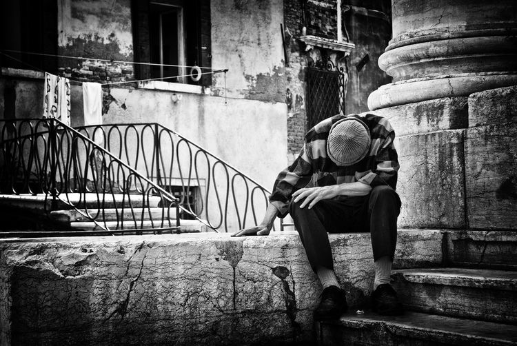 Man sitting on retaining wall against building
