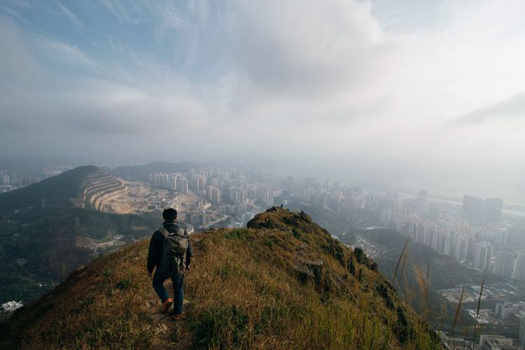 High angle view of hiker walking on mountain top against cityscape