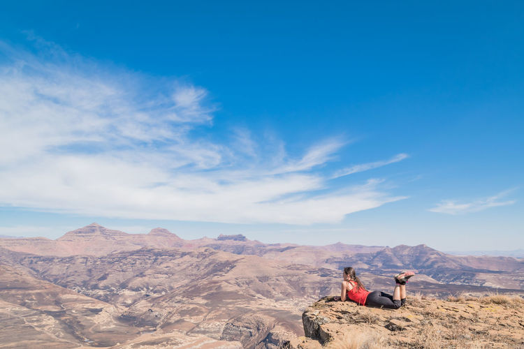 Woman Relaxing On Cliff Against Blue Sky