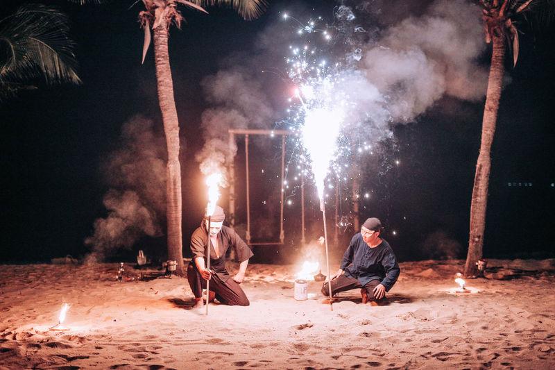 Man and woman sitting on bonfire