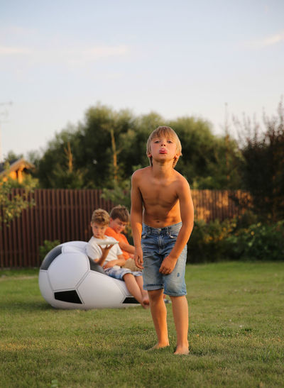 Portrait of boy teasing while standing on grass in yard