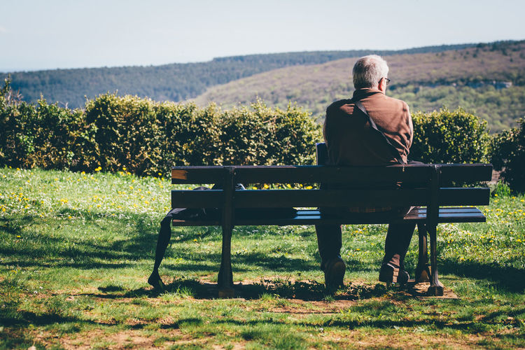 Rear View Of Senior Man Sitting On Bench Against Mountain