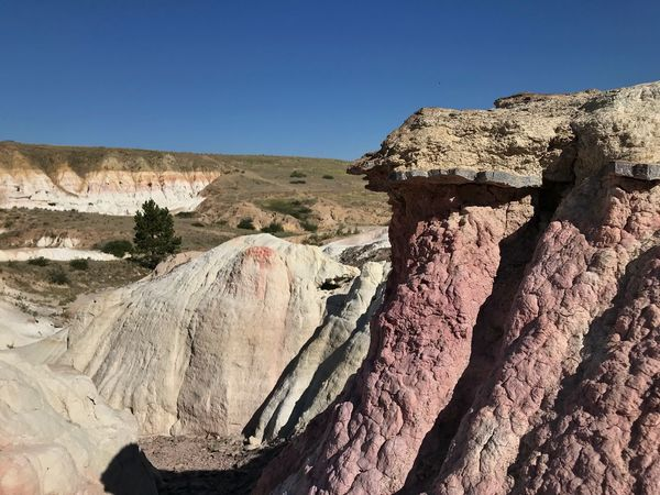 Landscape of pink and white rock formations or hoodoos in Colorado - Paint Mines Interpretive Park Hoodoos Pink Rocks Paint Mines Interpretive Park Colorful Rocks Colorado Sky Clear Sky Nature Land Sunlight Day No People Tranquility Tranquil Scene Landscape Blue Solid Rock Environment Scenics - Nature Desert Non-urban Scene Rock - Object Climate