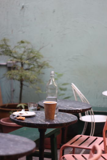 Bottle and disposable cup on table at restaurant