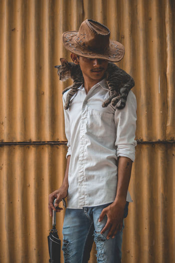 Adult Casual Clothing Cat Clothing Cowboy Cowboy Hat Day Front View Hat Iron Kitten Leisure Activity Lifestyles One Person Portrait Real People Standing Three Quarter Length Wall - Building Feature Wild West Young Adult