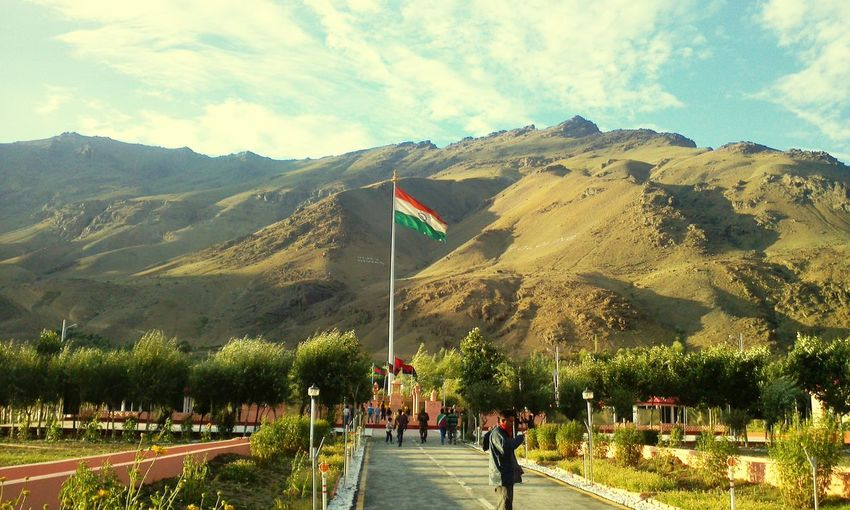 People standing on pathway with indian flag against mountains