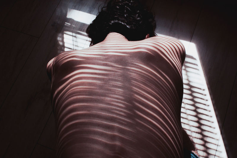 Rear view of man lying at home