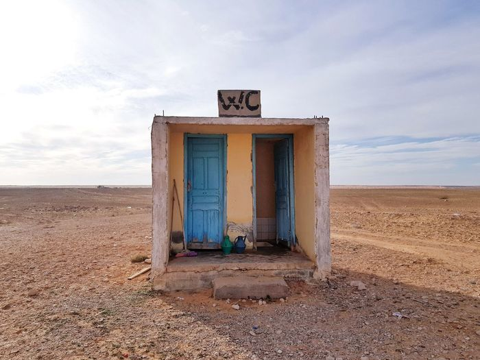 Abandoned Outhouse On Desert Against Cloudy Sky