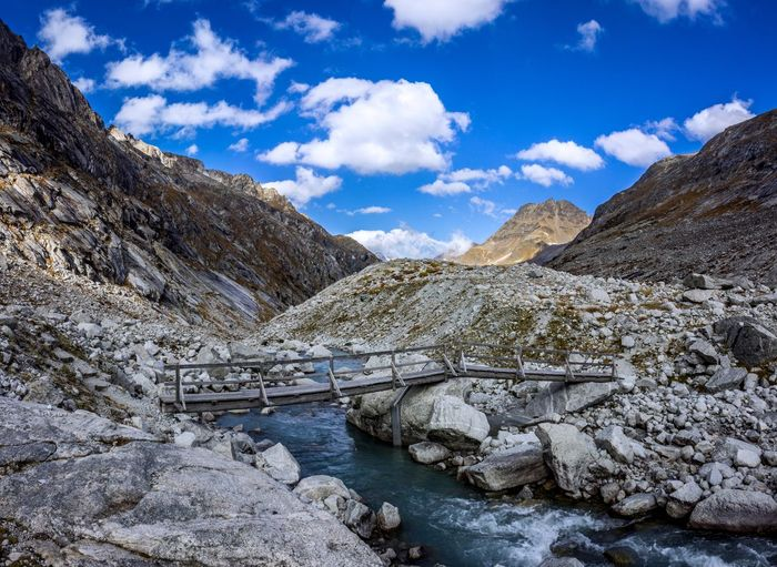 Footbridge over stream by mountains against cloudy sky