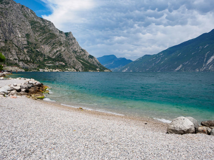 Pebble beach at Lago di Garda Dramatic Sky Lago Di Garda Pebble Beach Beach Cloud - Sky Clouds Day Italy Lake Landscape Mountain Nature No People Outdoors Pebble Scenics Sky Tranquil Scene Tranquility Water