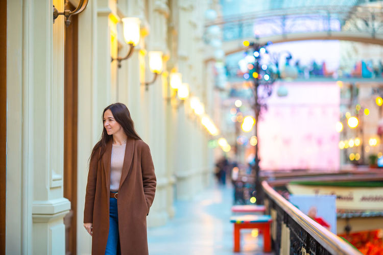 Beautiful smiling woman standing on footpath by building