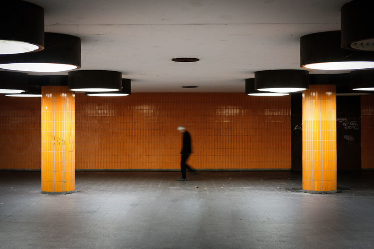 Side view blurred motion of man walking in subway