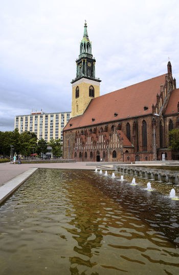 St. Mary's Church (Marienkirche) and water basin with fountain, a famous location and travel destination for tourists in Berlin Mitte, the capital city of Germany, copy space, vertical Basin Berlin Church City Mitte St Mary Church  Travel Architecture Building Building Exterior Capital City Clock Destination Fontaine Germany Landmark No People Outdoors Religion Sky Tourism Tower Water