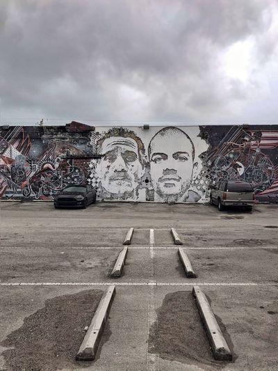 Graffiti on abandoned car against sky