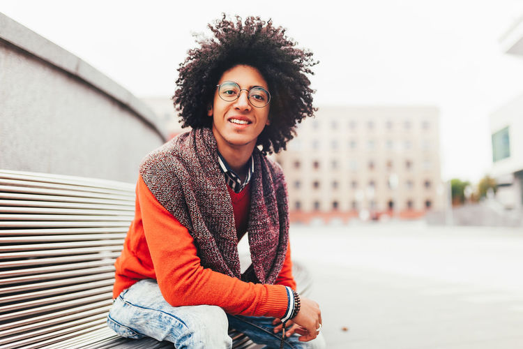 Portrait Of Afro Young Man Sitting On Bench In City