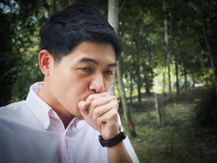 Man coughing against trees at forest