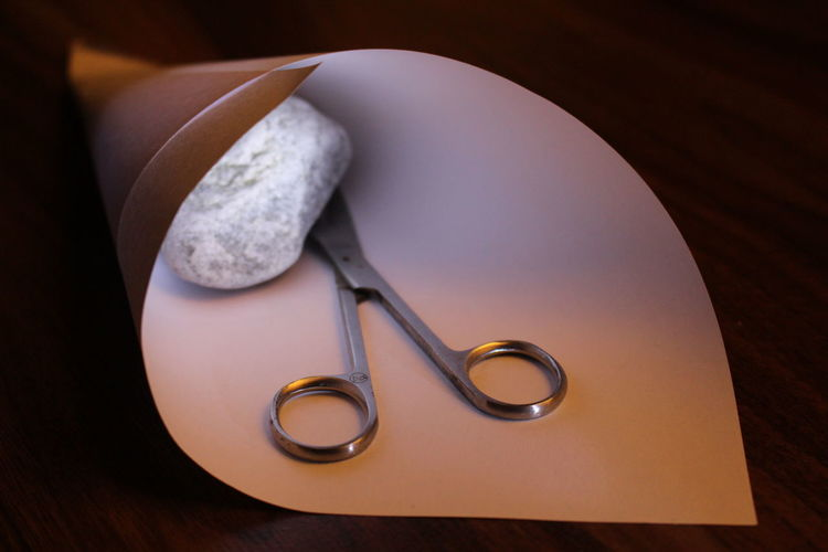 Close-up of scissor with stone in paper on table