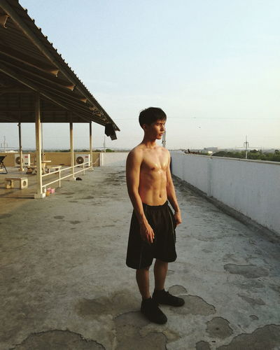 Full length of shirtless man standing on building terrace against clear sky