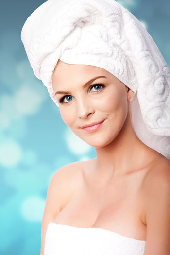 Portrait Of Young Beautiful Woman Wrapped In A Towel Against Blue Background