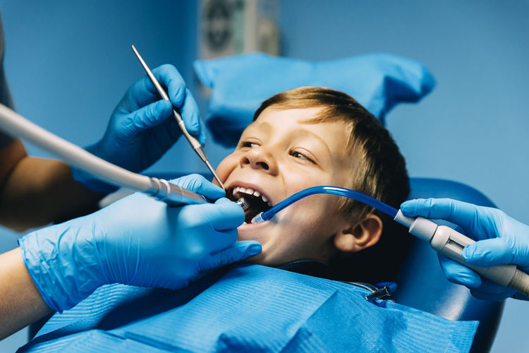 Cropped Hands Of Dentists Examining Boy At Clinic
