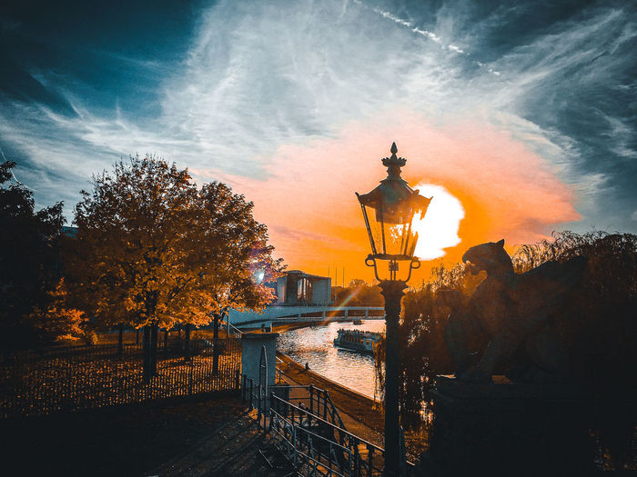 Illuminated street light by building against sky during sunset