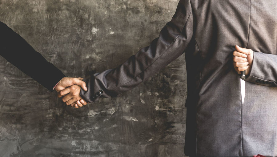 Close-up of businessmen shaking hands against wall