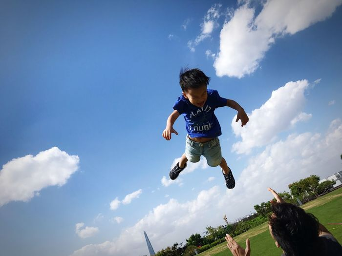 Rear view of father throwing son in mid-air at park