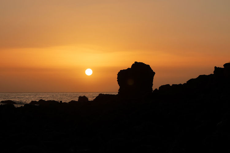 Silhouette rock formation by sea against orange sky