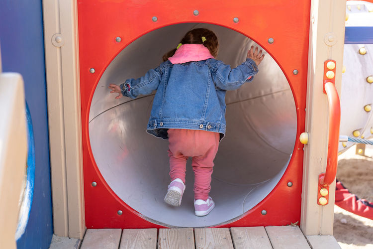 Rear view of girl walking on slide in playground