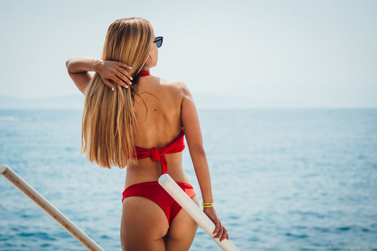 Sea Water Bikini Swimwear Rear View Clothing Hair Lifestyles Hairstyle Horizon One Person Leisure Activity Three Quarter Length Young Adult Real People Horizon Over Water Standing Young Women Outdoors