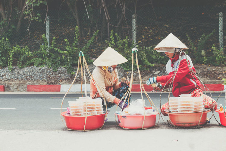 Unidentified Woman Monger Two People Hat Real People Container Women Adult Day Clothing Asian Style Conical Hat People Sitting Lifestyles Nature Tree Togetherness Holding Food And Drink Bucket Plant Vietnam Vacations Vietnamese Food Vietnamese Local Food Monger