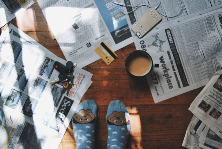 Low section of person in socks by tea amidst newspapers on floorboard