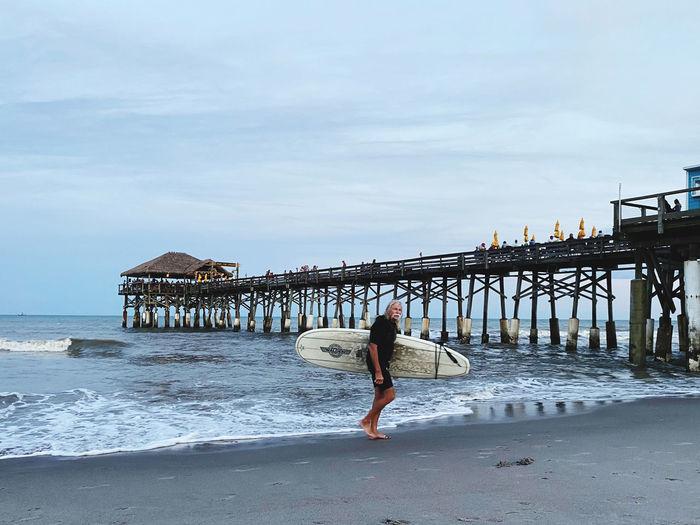 Woman on pier at beach against sky