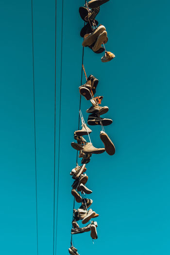 Sneakers hanging on cable line Blue Sky Day Nature Clear Sky No People Outdoors Arts Culture And Entertainment Sport Sneakers Power Line  Hanging Shoes Shoelace Art Wire