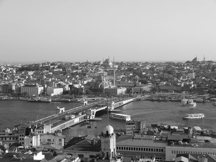 Aerial view of strait amidst buildings against clear sky