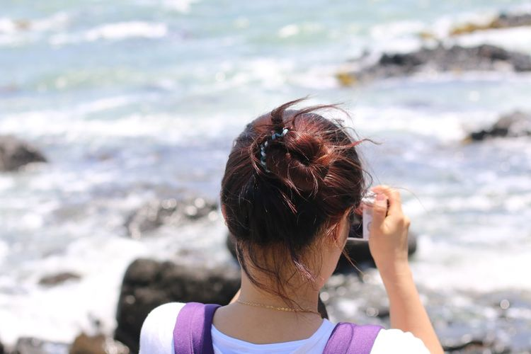 Rear view of woman photographing sea