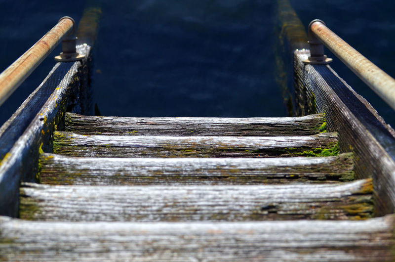 Old staircase made of wood going down to the water. Antique Built Structure Business Cloud - Sky Color Day Diminishing Perspective Ladder Nature No People Old Outdoors Part Of Protection Railing Selective Focus Staircase Stairs Stairway Steps Steps And Staircases The Way Forward Vanishing Point Water Wood - Material