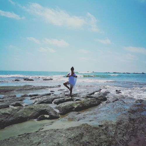 Mid adult woman meditating while standing at beach against sky