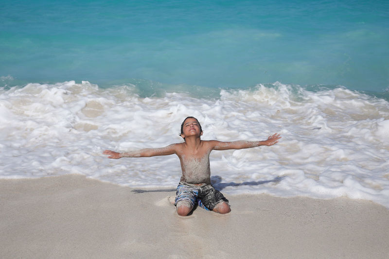 Shirtless Boy With Arms Out Stretched Relaxing On Shore At Beach