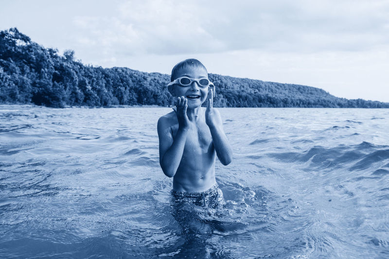 Portrait of shirtless boy in lake against sky