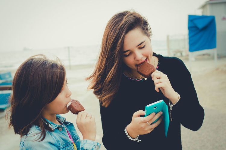 Sisters eating ice cream while using mobile phone