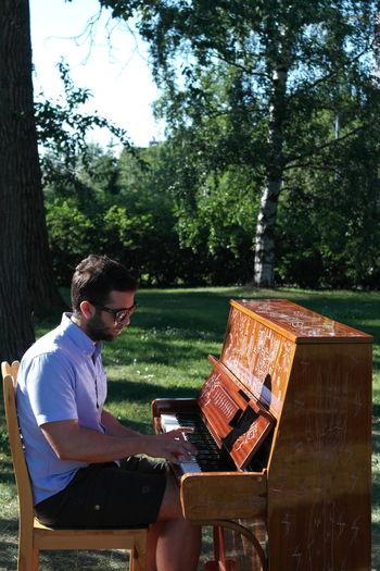 Man playing piano in garden